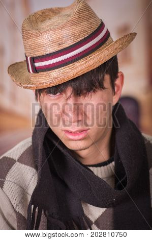 Close up of a sad homeless young man in the streets, wearing a hat and a scarf, in a blurred background.