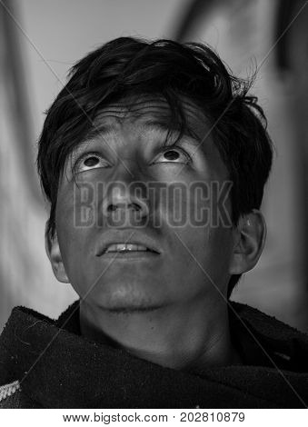 Close up of a handsome homeless young man in the streets, looking to the the sky, in a blurred background.
