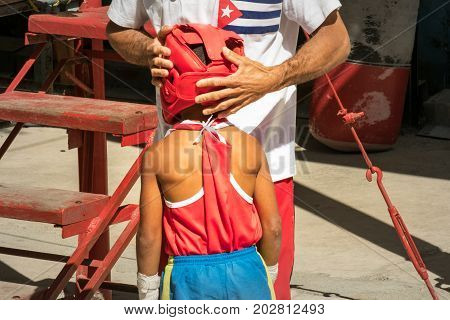 Adult helping a junior boxer prepare for the ring in Cuba