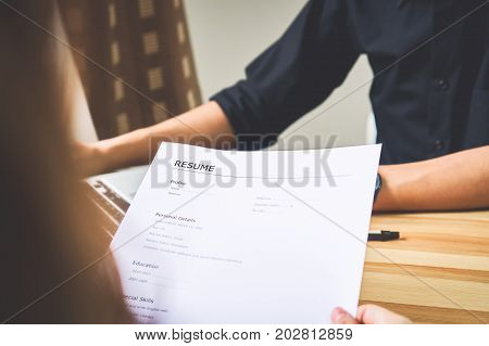 Young woman submit resume to employer to review job application. The concept presents the ability for the company to agree with the position of the job.