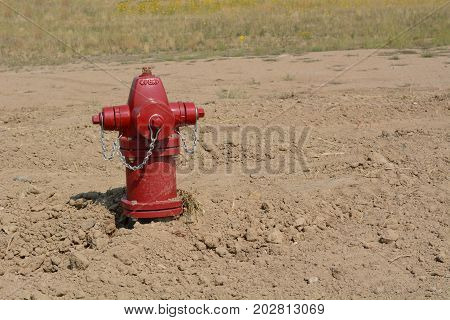 Red fire hydrant in empty field on bulldozed shopping center under new development and revitalization