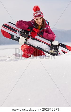 Standing beatiful young woman with a pink snowboard on snow.