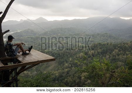 Kalibiru National Park, Jogjakarta Indonesia: August 19th 2017 - Shot of a person sitting on a wooden platform enjoying the vast view of Kalibiru National Park in Jogjakarta Indonesia