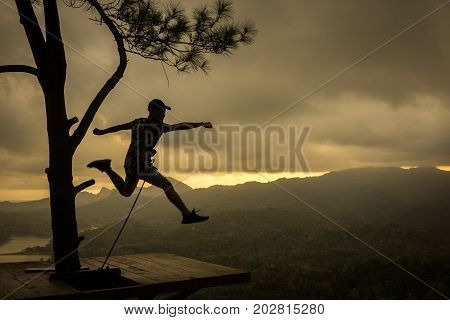 Kalibiru National Park, Jogjakarta Indonesia: August 19th 2017 - A silhouette shot of a person jumped on a wooden platform at Kalibiru National Park Jogjakarta Indonesia