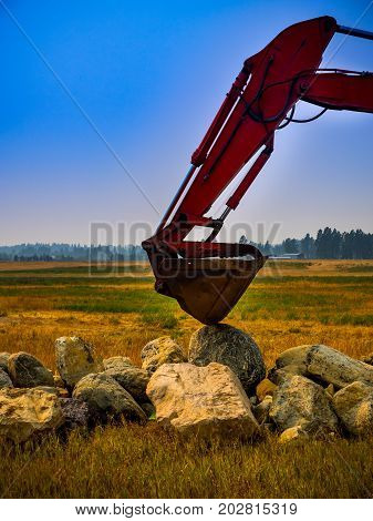 An excavator resting its bucket on a pile of boulders.