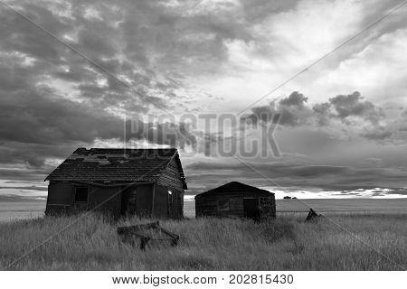 A black and white image of an old run down homestead under stormy skies.