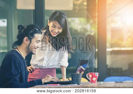 happiness emotion of asian younger man and woman freelance team working with computer laptop in home office