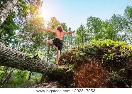 Young man standing on one leg on a tree trunk in the forest. Sportsman relaxing with arms wide open.