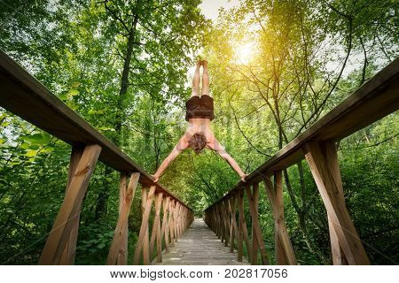 Young man doing a handstand on a footbride in the forest. Summer outdoor activity. Low angle perspective.