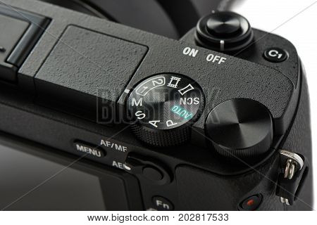 Closeup of mode selection dial on a Mirrorless Camera isolated on white.