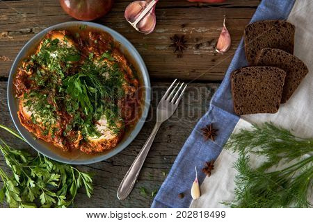 Shakshuka - Jewish Traditional Recipe. Breakfast With Fried Eggs, Tomato Sause, Pepper And Green