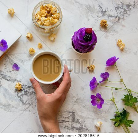 Woman's Hand With Cup Of Coffee, Popcorn, Wild Flowers And Violet Cupcake. Top View, Life Style.