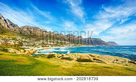 The Twelve Apostles, which are on the ocean side of Table Mountain at Cape Town South Africa and the beach community of Camps Bay between the mountain and the Pacific Ocean