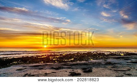Sun setting under orange sky over the horizon of the Atlantic Ocean at Camps Bay near Cape Town South Africa on a nice winter day