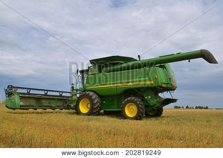 MOORHEAD, MINNESOTA, August 14, 2017: The self propelled green combine combine parked in the stubble of a wheat field is a product of John Deere Co, an American corporation that manufactures agricultural, construction, forestry machinery, diesel engines,