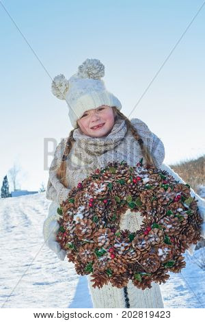 Child standing on the snow holding advent wreath for christmas