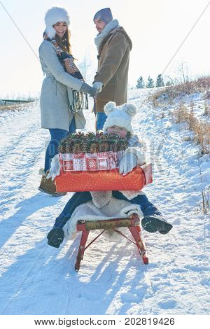Family delivering christmas gifts in winter with sled