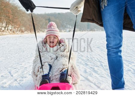 Child laughing and having fun while sledding with her family in winter