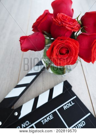 Vintage Classic Clapperboard On Brown Wooden Table Whis Red Roses