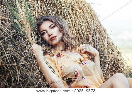 close up portrait of beautiful woman in field with haystacks