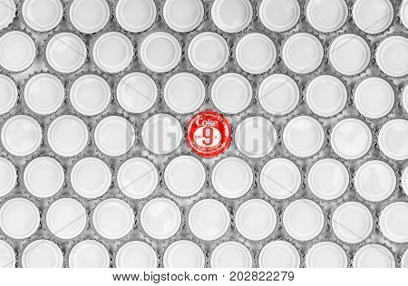 BANGKOK Thailand - Aug 30 2017: Thai red Coca Cola crown cork bottle cap (with logo and price) in the center of black and white cap pattern background aluminum texture lid of soda beverages