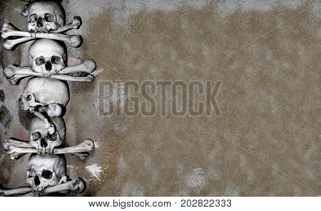 Halloween grunge background with human skulls and bones and old wall stucco texture