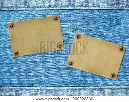Background with jeans texture of blue color and two leathers labels. Copy space for your text
