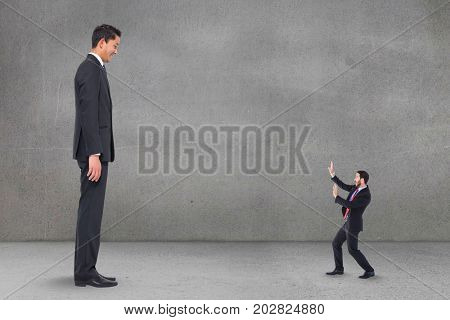 Digital composite of Scared small business man looking at a big business man