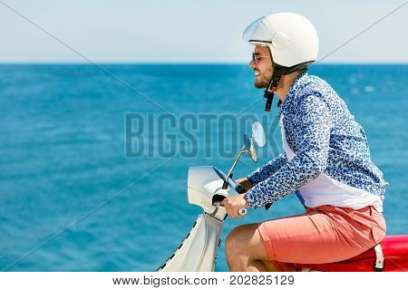 Handsome man posing on a scooter in a vacation context. Street fashion and style