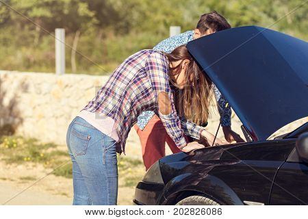 Young couple after a car breakdown at the side of the road.