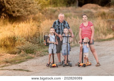 Family walk on scooters with his wife and children on the village road near Volgograd area