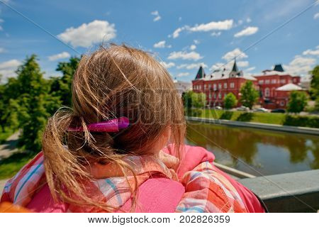 Back view of young female tourist looking at famous palace. Russia, Orel city orlik embankment state bank building