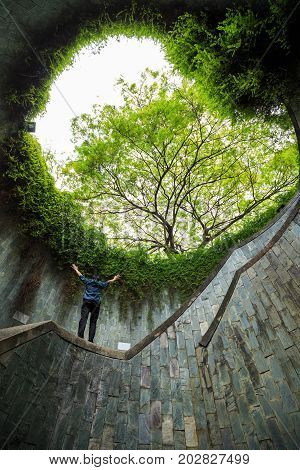 man hands up at underground crossing in tunnel at Fort Canning Park Singapore