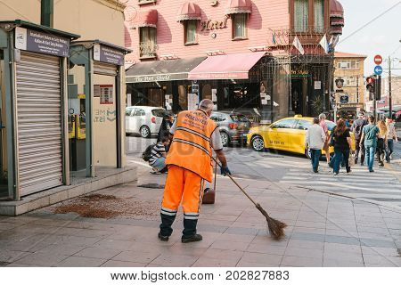 Janitor in bright orange uniform sweeping the tile on the street in Sultanahmet district in Istanbul, Turkey. Pedestrians crossing the road in the background.