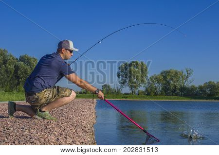 Area Trout Fishing. Fisherman With Spinning Rod In Action Playing Fish.