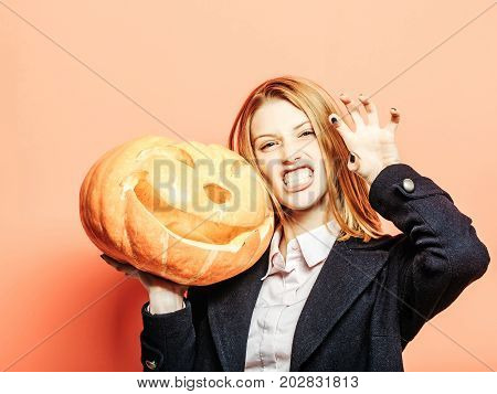 Halloween woman with happy face. Party and traditional food. Girl with scary pumpkin. Holiday and celebration. Woman in coat and scarf at orange wall.