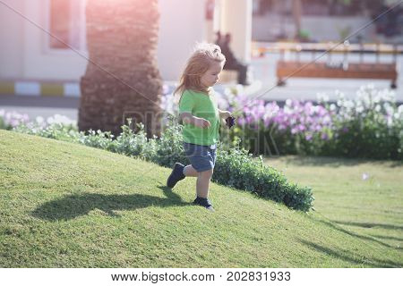 Little child boy with adorable serious face long blond hair in green shirt and blue shorts running at grass meadow on background of blossoming flowers at sunny summer day