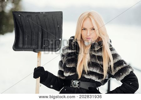 Woman standing with snow shovel in hand on winter day. Girl with long blond hair wearing fur jacket on white snow landscape. Christmas and new year. Holidays celebration concept.
