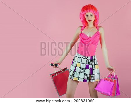 Girl wearing red wig and fashionable clothes. Sale and black friday. Fashion shopper posing on pink background. Holidays celebration concept. Woman with shopping bags copy space