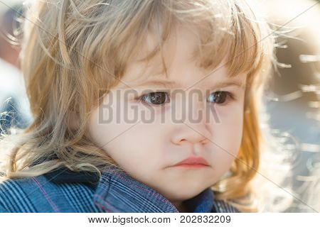 Kid with long blond hair. Baby on sunny day outdoors. Happy childhood concept. Toddler boy with cute face. Child with brown eyes.