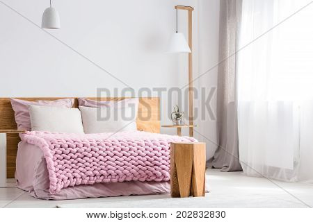 A wooden table and lamp stands next to king-size bed with pink overlay