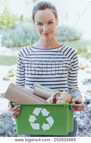 Smiling aware woman holding a green container with segregated paper junk. Segregating paper waste concept.