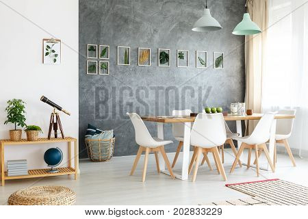 Small wooden table with telescope books and potted plants in modern dining room