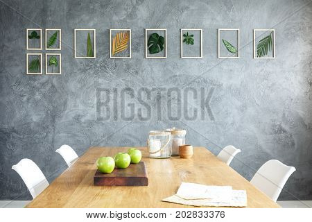 Framed leaves hanging on the raw grey wall in stylish dining room