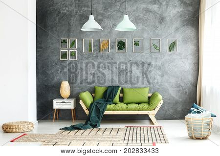Dark green blanket thrown on wooden couch standing in living room with wicker basket and footrest