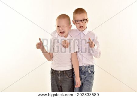 A caucasian elementary age boy with glasses posing in uniform isolated on white background with him brother. School and education concept.