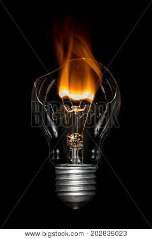 Broken light bulb with flame on black background .