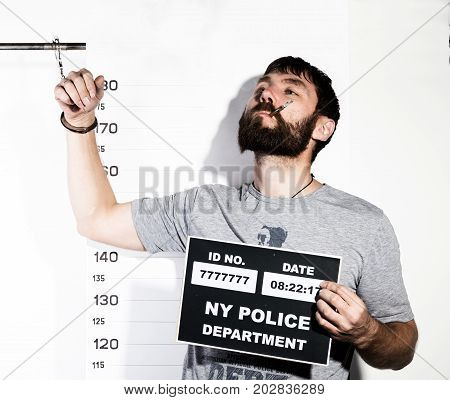 bearded man in handcuffs with sigarette, Criminal Mug Shots.