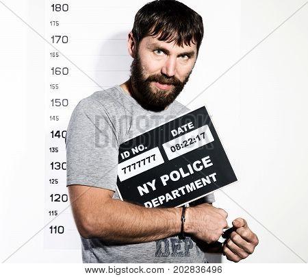 bearded man in handcuffs holds a sign, Criminal Mug Shots.