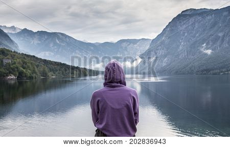 Solitary woman wearing purple hoodie watching tranquil overcast morning scene at lake Bohinj, Alps mountains, Slovenia.